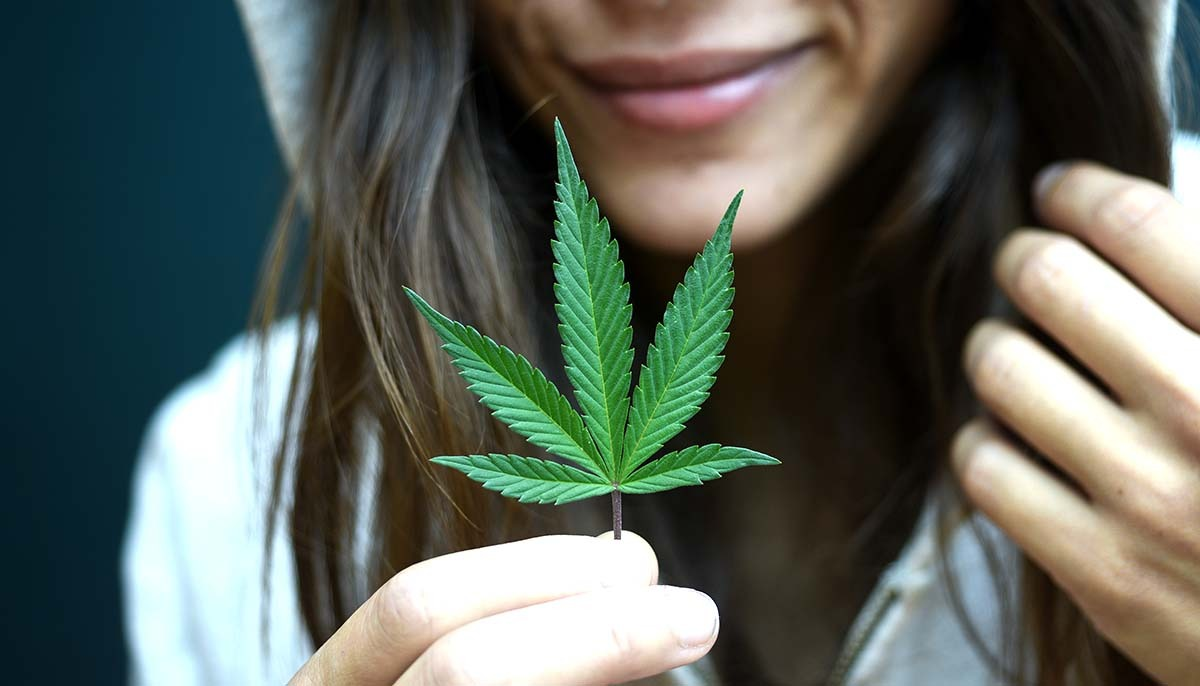 Smiling woman holding cannabis leaf